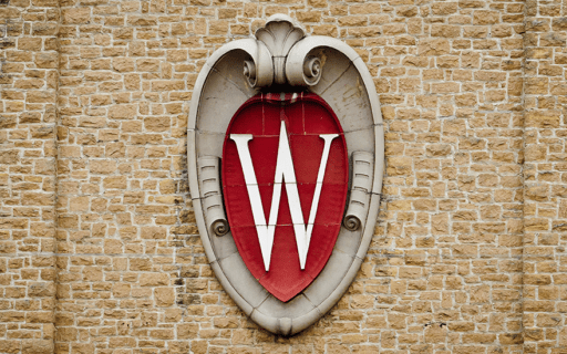 The UW-Madison crest engraved in stone along a brick wall.