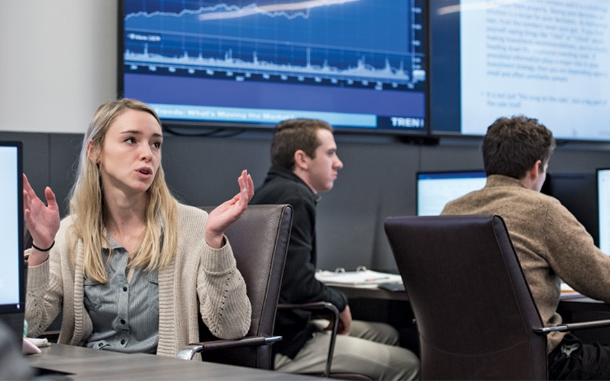 Student speaking in front of screen in finance and analytics lab