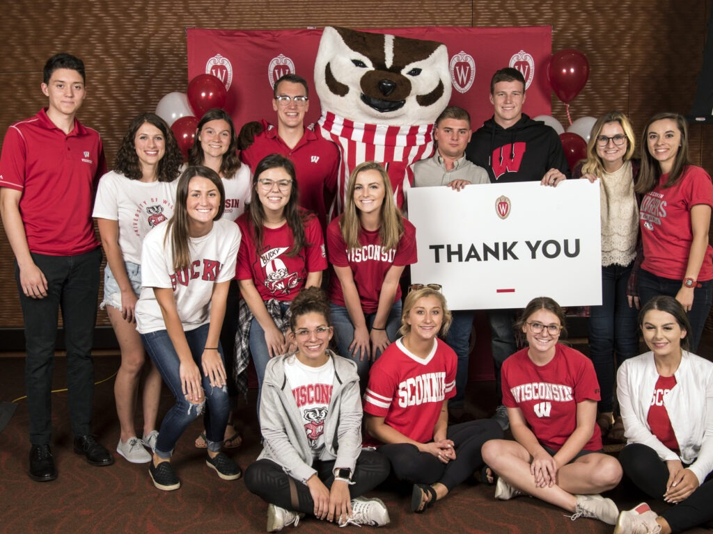 Students holding a Thank You sign with Bucky Badger