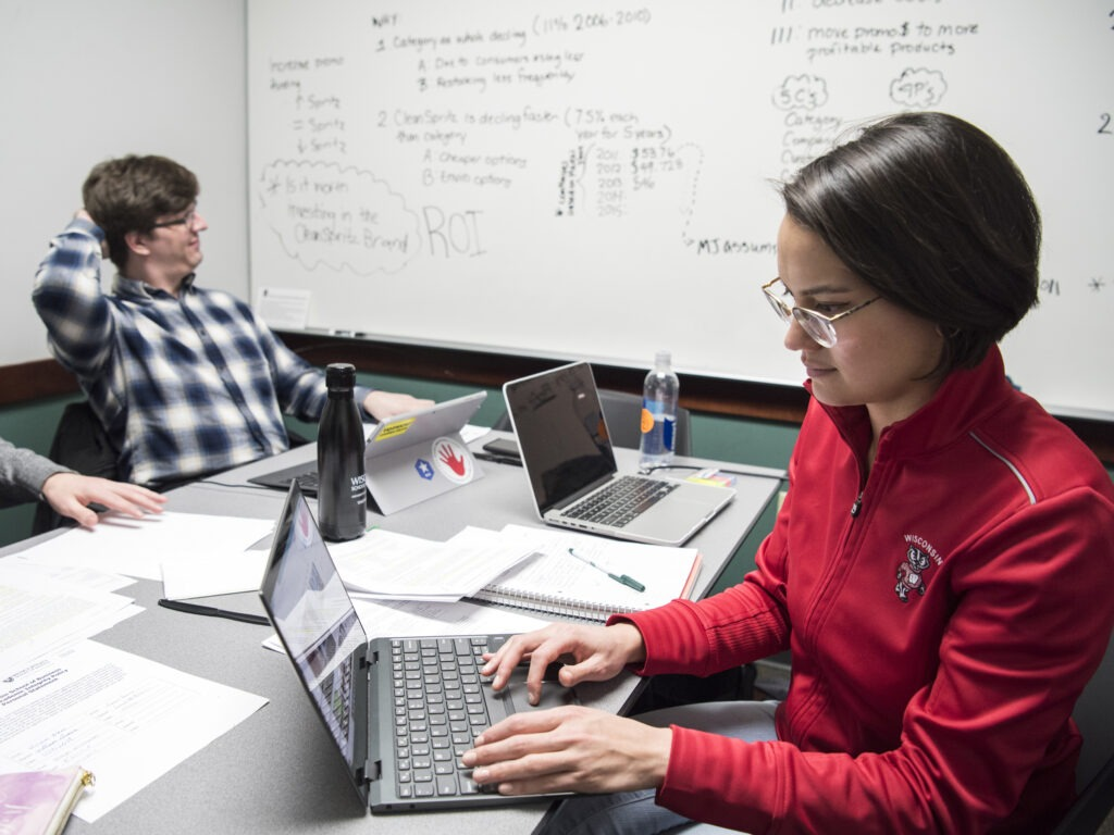 A student working on a laptop, another student looking at a whiteboard