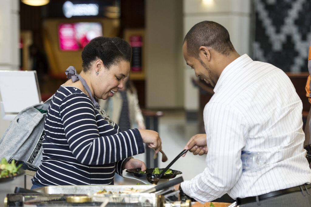 (L to R) Ashligh Coaxum and Justin Johnson, both first year MBA students, grabs a bite to eat with Tosan Olley (2nd year MBA student) and a hardy laugh before heading into the Lunch and Learn event on Wednesday, April 29, 2015.