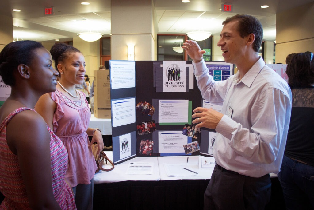 Two women talking with a man at the Student Organization Fair