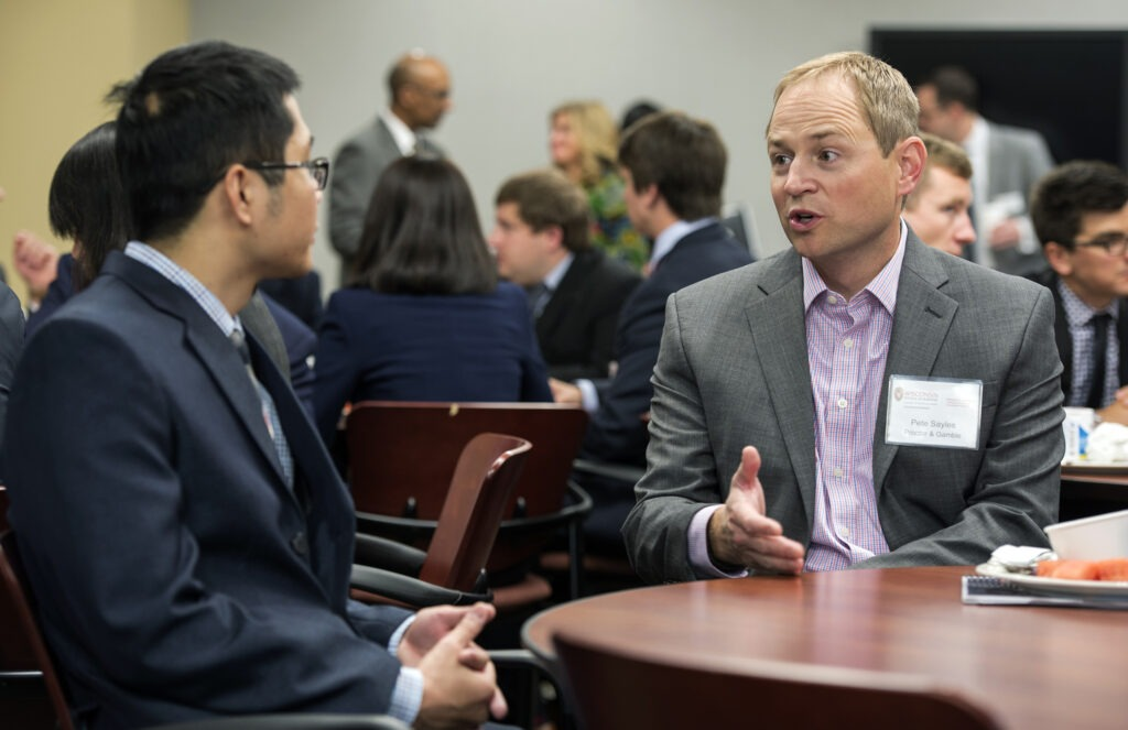 Advisory board members speak with MBA students at a board meeting