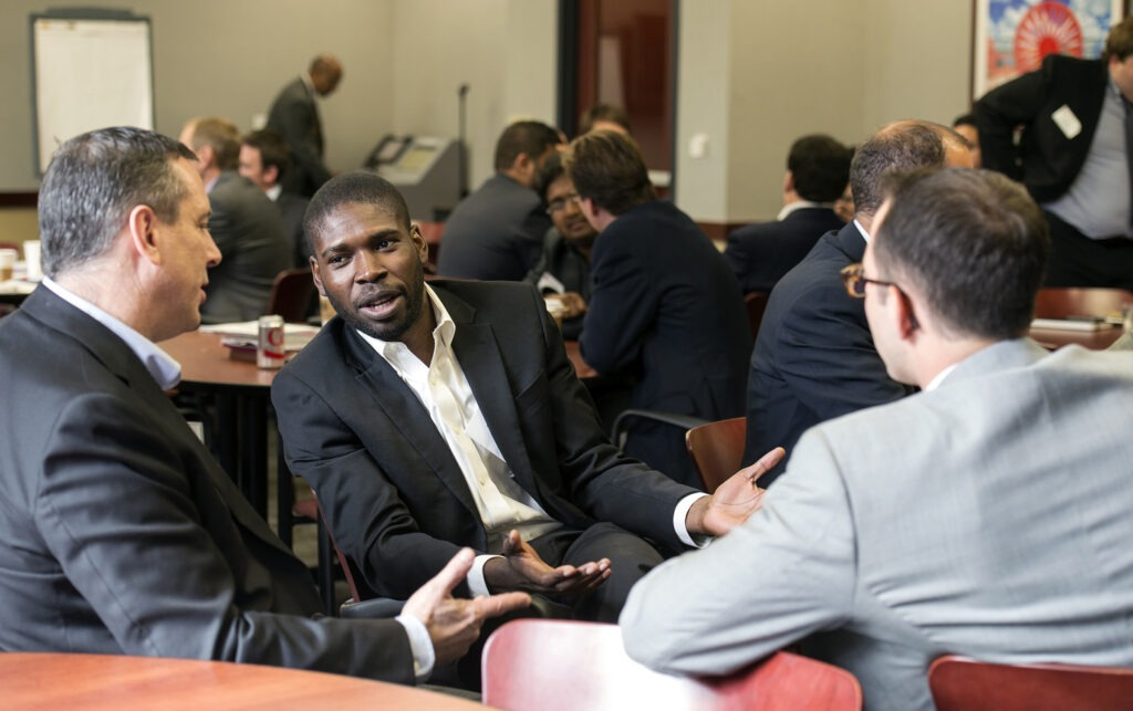 Board members talk with MBA students at a board meeting