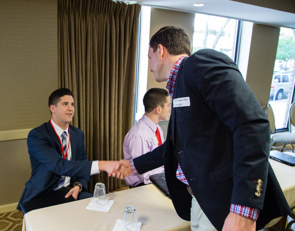 people shaking hands at networking event