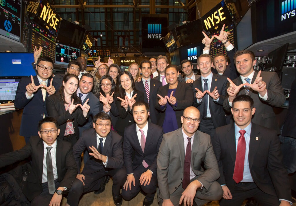 group of students posing in front of stock exchange