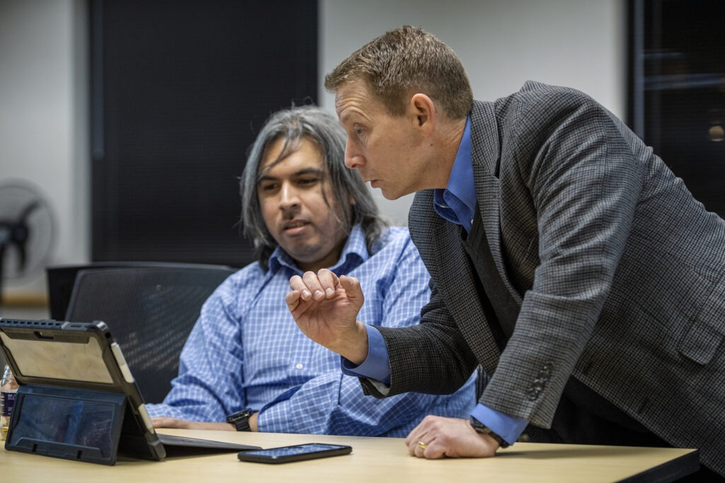 Two people working over laptop