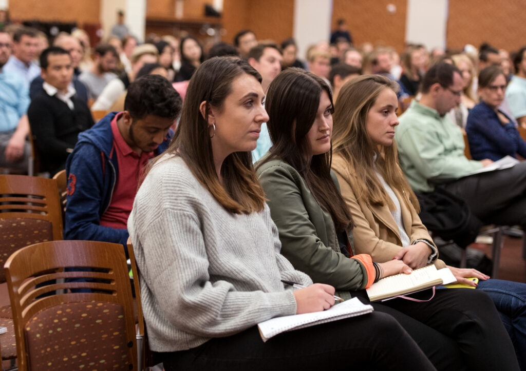 Students taking notes in an auditorium