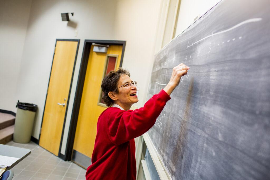 Professor Margie writing on a chalkboard