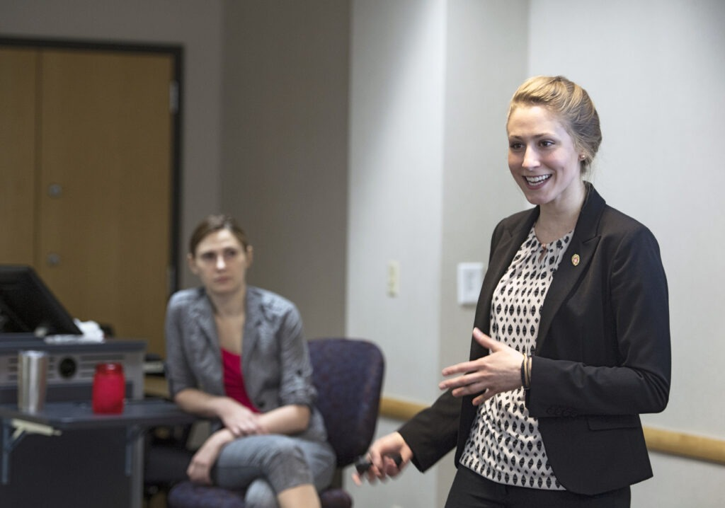 MBA student watches her teammate present their project at an event