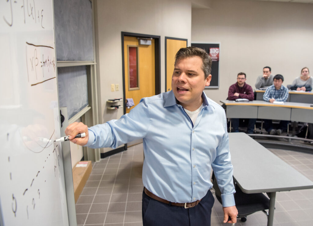 Instructor Dani Bauer writing on a whiteboard as he is teaching a class