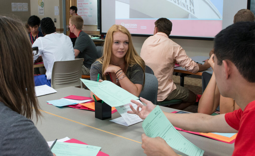 A woman handing out papers to students sitting at a table