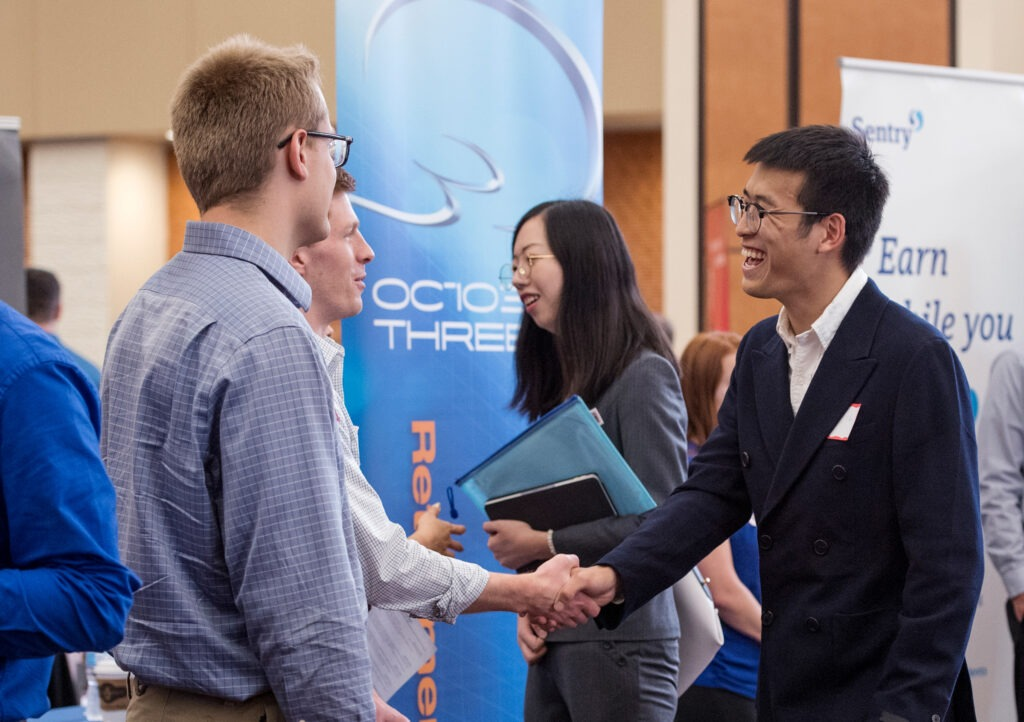 Two men shaking hands at the Risk and Insurance career fair