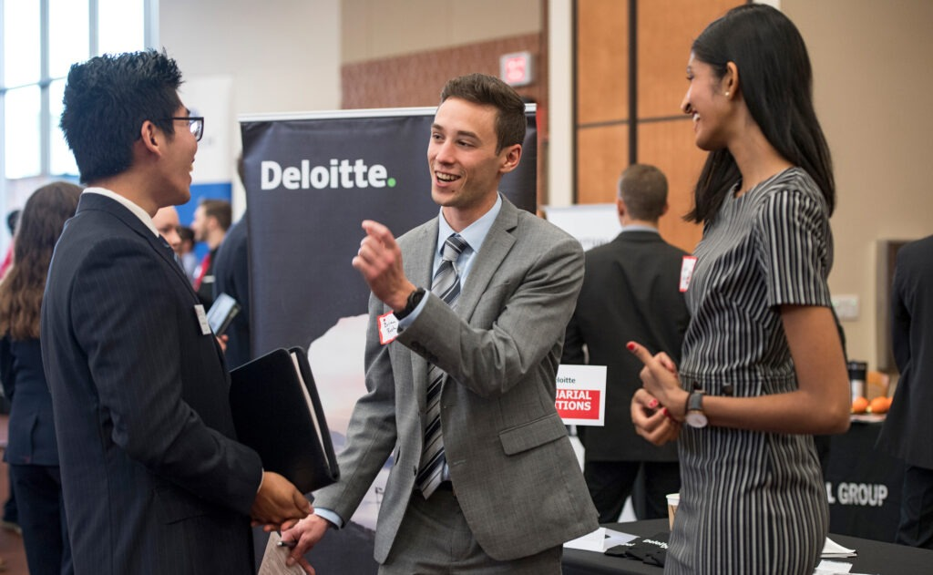 A man talking with another man and woman at Risk and Insurance Career Fair