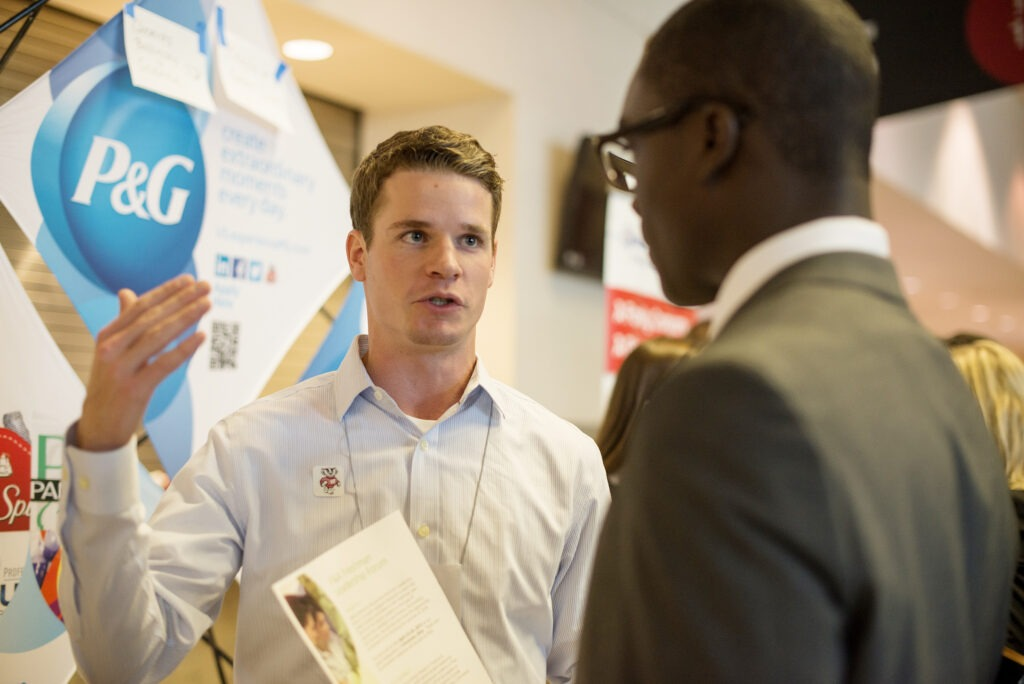 Two men talking at a career fair event