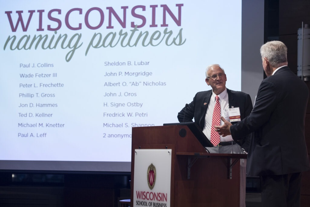 Two men on a stage with Wisconsin naming partners on the screen behind them.