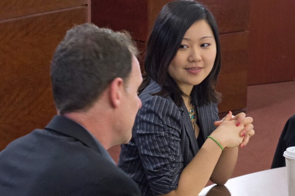 A woman smiling at a man while both are sitting at a table